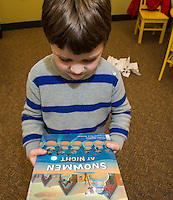 "Luke Dorval-Drown holds the book ""Snowmen At Night"" read during Laconia Library's preschool story hour on Wednesday morning.  (Karen Bobotas/for the Laconia Daily Sun)"