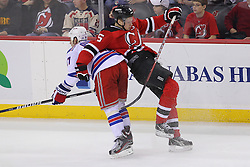 Jan 31; Newark, NJ, USA; New York Rangers left wing Brandon Dubinsky (17) hits New Jersey Devils defenseman Adam Larsson (5) during the third period at the Prudential Center.  The Devils defeated the Rangers 4-3 in an OT shootout.