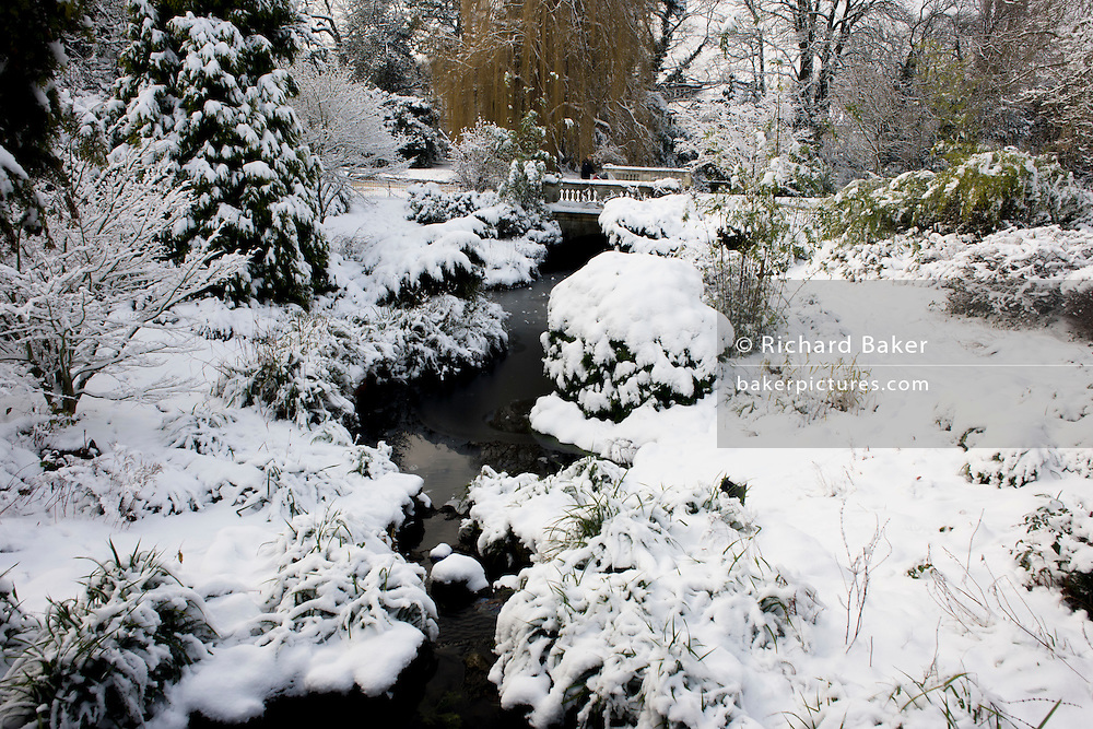 Frozen water feature and bridge landscape in Dulwich Park, south London during mid-winter snow.
