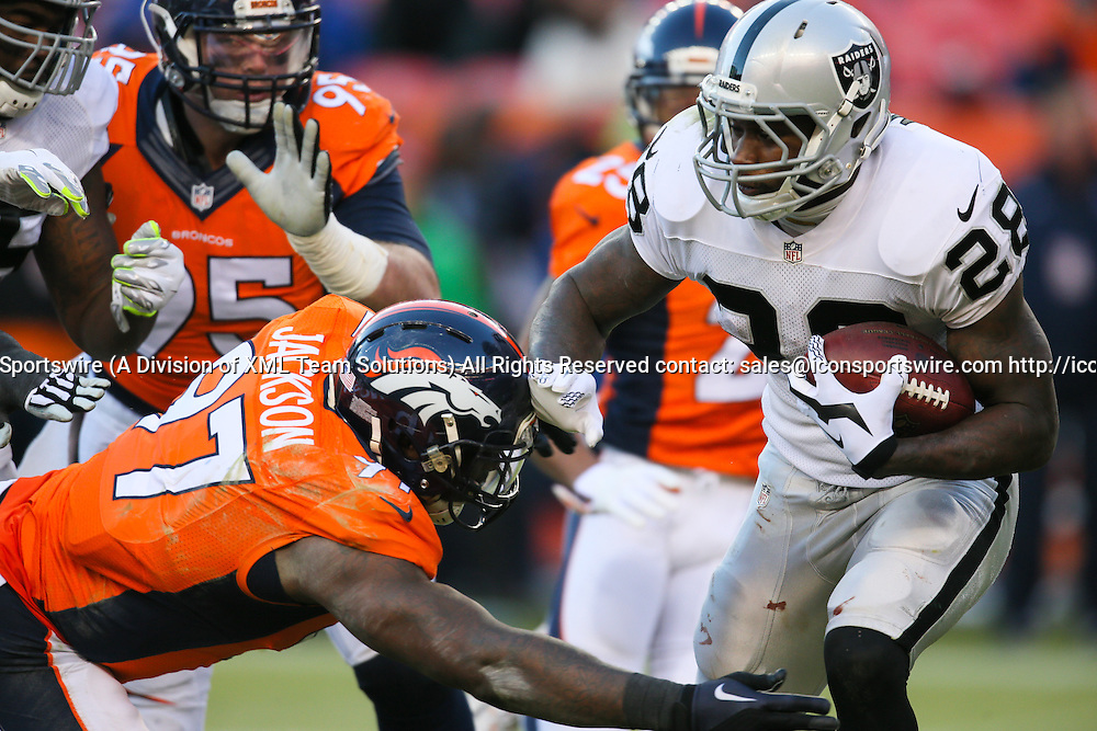 28 December 2014: Oakland Raiders running back Latavius Murray (28) runs with the ball as Denver Broncos defensive end Malik Jackson (97) attempts a tackle.  The Denver Broncos defeated the Oakland Raiders by a score of 47 to 14 at Sports Authority Field at Mile High, Denver, CO.