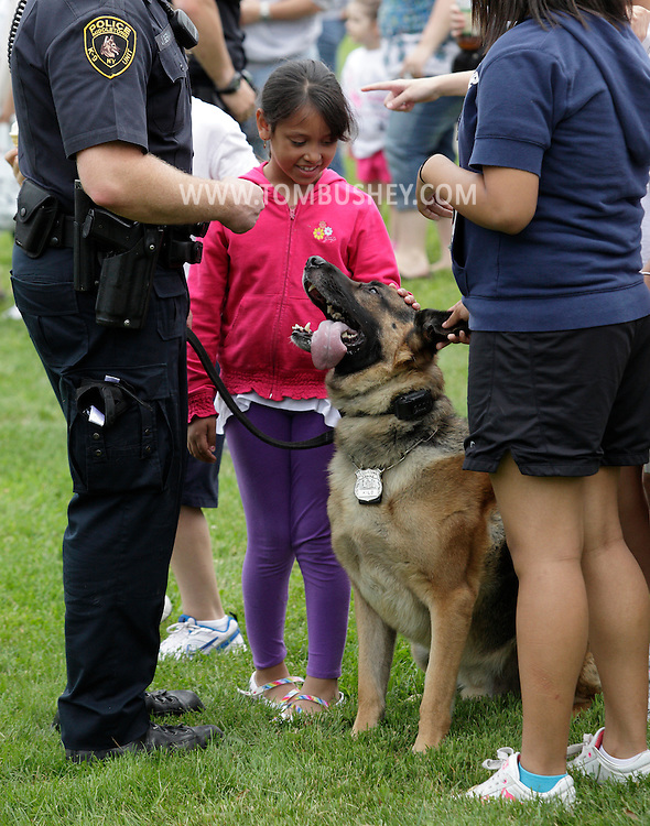 Middletown, New York - A young girl pets police dog Kilo at the festival following the 15th annual Ruthie Dino Marshall 5K Run and Fun Walk hosted by the Middletown YMCA on Sunday, June 5,  2011.