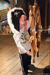 United States, Washington, Bellevue, KidsQuest Children's Museum, boy in prate hat turning ship's wheel