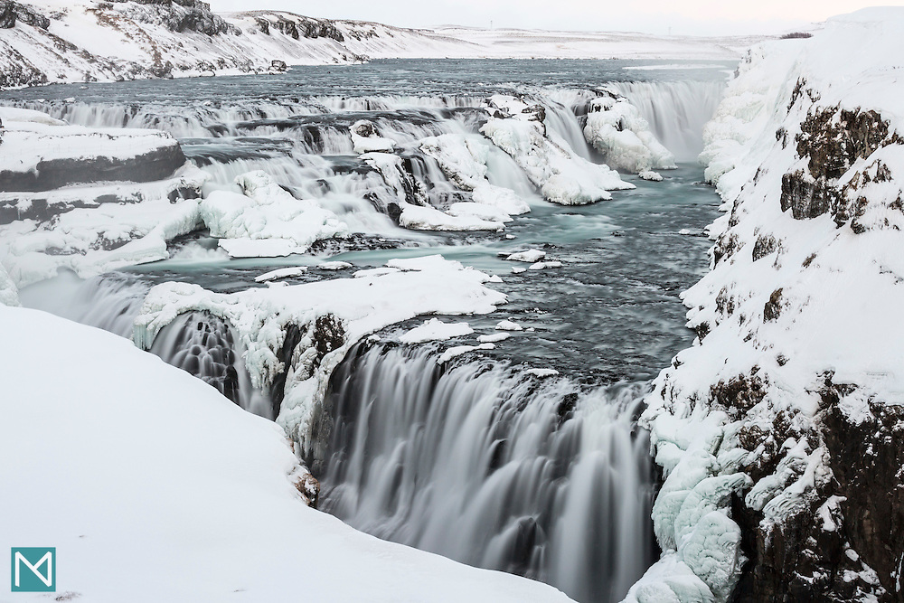 Gullfoss waterfall in winter clothes, where the Hvítá river falls down two cascades into a deep canyon at the edge of the Icelandic highlands.