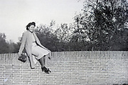 happy smiling Indonesian woman sitting on a brick wall Netherlands 1950s