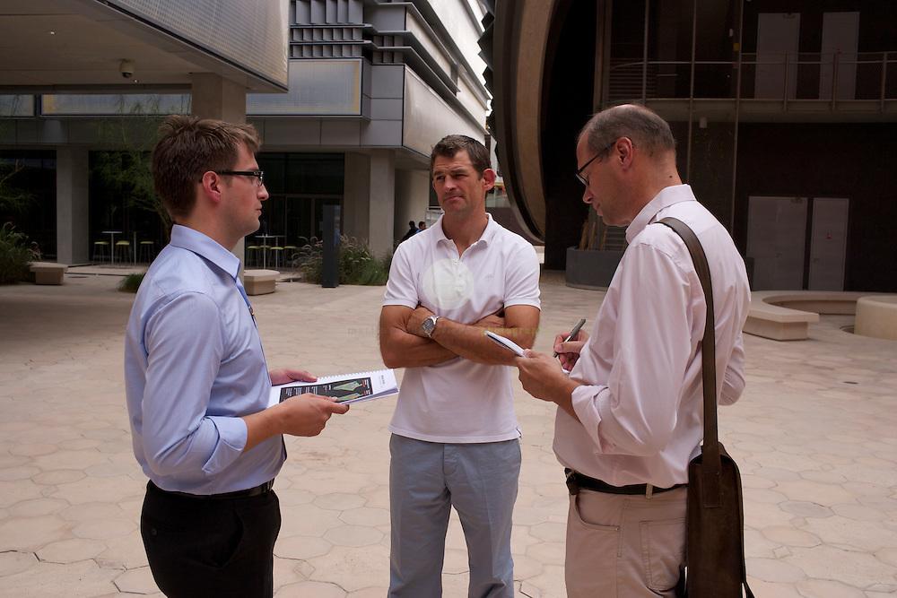 Masdar City. ASIEN, VEREINIGTE ARABISCHE EMIRATE, EMIRAT ABU DHABI, ABU DHABI, 14.04.2011: SPIEGEL-Korrespondent Alexander Smoltczyk (rechts) im Gespraech mit den Architekten Juergen Haepp (links) und Austin Relton, auf dem Campus des Masdar Institutes . Die Wu?stenstadt Masdar sollte das Silicon Valley fu?r nachhaltige Technologien werden. 2006 rief Scheich Mohammad Bin Zayed al-Nahyan, Kronprinz von Abu Dhabi, das Projekt ins Leben. Die Fertigstellung des Projekts wird sich verzoegern: statt wie geplant 2016 wird die Oekostadt fruehestens 2025 fertig.. - Stichworte: Nachhaltigkeit, Masdar, City, Emirat, Vision, Zukunft, Arabien, Stadt, Oekologie, Gruen, Planung, Foster, Architekt, Wueste, Umwelt, Technik, Universitaet, Alexander, Smoltczyk, Gespraech, Interview, Juergen, Haepp, Austin, Relton