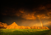 Most of the rainfall in the Badlands region falls in the period from May to July, often in the form of powerful storms, sometimes loosely referred to as monsoons. If the storms occur at sunrise or sunset, the light on the landscape can be dramatic. Badlands National Park in South Dakota, USA.