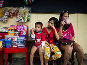 20 JANUARY 2018 - CAMALIG, ALBAY, PHILIPPINES: CHRISTIAN JAY NAAG, 4, left, his cousin, ANGELICA DENISE ALUARIN, 10, and Angelica's mother JOSIE ALUARIN, sit next to a candy stand at the Barangay Cabangan evacuee shelter in a school in Camalig. There are about 650 people living at the shelter. They won't be allowed to move back to their homes until officials determine that Mayon volcano is safe and not likely to erupt. More than 30,000 people have been evacuated from communities on the near the Mayon volcano in Albay province in the Philippines. Most of the evacuees are staying at school in communities outside of the evacuation zone.   PHOTO BY JACK KURTZ