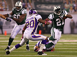 Oct 11, 2010; East Rutherford, NJ, USA; New York Jets running back LaDainian Tomlinson (21) avoids a tackle by Minnesota Vikings safety Madieu Williams (20) during the first half at the New Meadowlands Stadium.