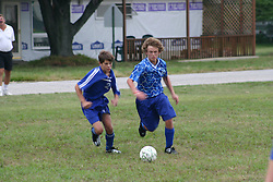 Soccer players battle for control of ball