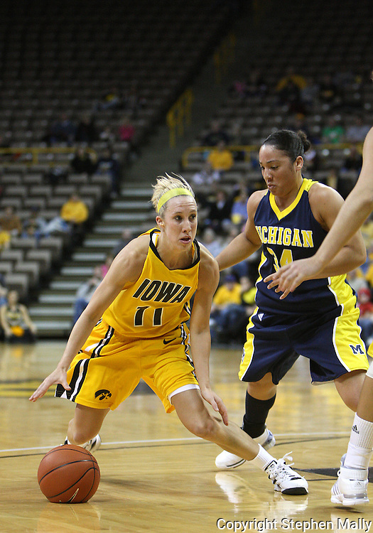 26 JANUARY 2009: Iowa guard Kristi Smith (11) tries to drive inside while being guarded by Michigan guard Jessica Minnfield (34) during the first half of an NCAA women's college basketball game Monday, Jan. 26, 2009, at Carver-Hawkeye Arena in Iowa City, Iowa. Iowa defeated Michigan 77-69.