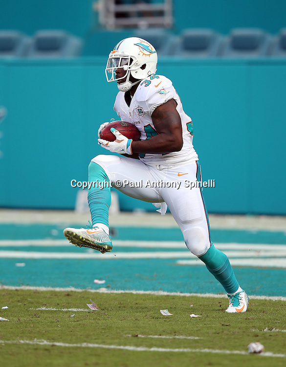 Miami Dolphins running back Damien Williams (34) high steps as he returns a kickoff during the 2015 week 13 regular season NFL football game against the Baltimore Ravens on Sunday, Dec. 6, 2015 in Miami Gardens, Fla. The Dolphins won the game 15-13. (©Paul Anthony Spinelli)