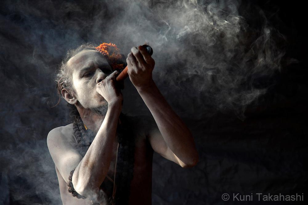 Sadhu (holy man) smokes in Haridwar, India on Feb 2010 during Kumb Mela, largest Hindu gathering in the world.<br /> Photo by Kuni Takahashi