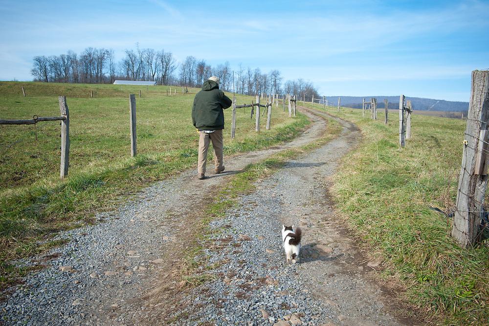 Man walks winding dirt road.