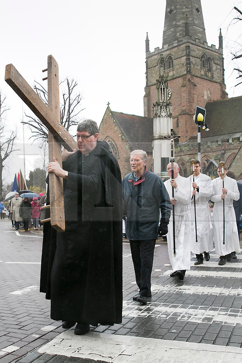 """3/4/2015. Solihull, West Midlands, UK. The Good Friday """"Walk of Witness"""" taking place in Solihull. People of all faiths congrgate outside St Alphege Church and walk the short distance to Mell Square to hold a multi-faith prayer meeting. Pictured, The cross begins it's journey through Solihull. Photo credit : Dave Warren/LNP"""