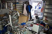 Ransacked and looted. A friend of the owner assess the damage inside Clarence convenience store and off license trashed by rioters. Pembury estate, Hackney, London.