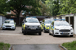© Licensed to London News Pictures. 26/05/2018. Crawley, UK. Police vehicles are seen parked at some garages near a block of flats in Crawley where a woman was found dead.  A man has been arrested on suspicion of murder after the woman was found in her bed. Police are appealing for witnesses to come forward.  Photo credit: Peter Macdiarmid/LNP