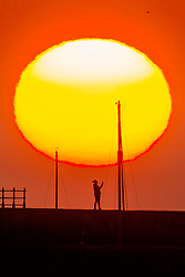 © Licensed to London News Pictures. 25/05/2020. Scarborough UK. A woman takes a selfie at Scarborough harbour while watching the sunrise this morning on the Yorkshire coast. Photo credit: Andrew McCaren/LNP