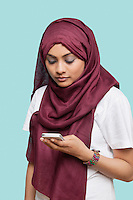 Young Muslim woman in traditional clothing text messaging against blue background