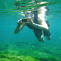 Man taking a photo underwater in a cenote.