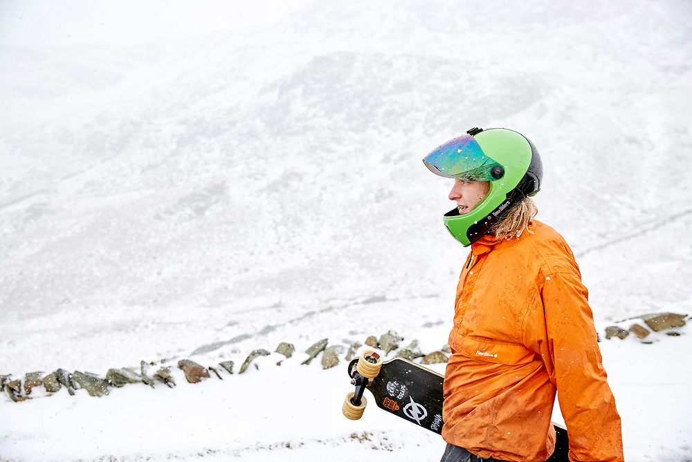 A photograph of a downhill skateboarder in winter conditions on the struggle, near kirkstone pass in Cumbria, England.