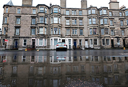 Tenement apartment buildings reflected in large puddle after heavy rain in Edinburgh, Scotland, UK