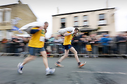 © Licensed to London News Pictures. 28/03/2016. Gawthorpe UK. The 2016 World Coal Carrying Championships took place today despite Storm Katie battering Yorkshire. The race see's male competitors carry 50kg of coal & the Ladies 20kg, they start from the Royal Oak pub & race 1 mile to the Maypole Green in Gawthorpe Village. Photo credit: Andrew McCaren/LNP