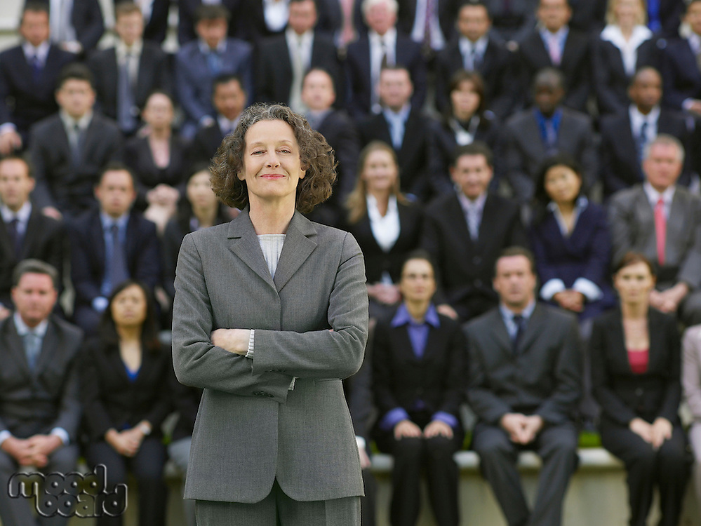 Business woman standing in front of business people sitting in bleachers portrait