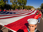 "11 NOVEMBER 2013 - PHOENIX, AZ: A US Navy sailor helps carry an American flag at the Phoenix Veterans Day parade. The Phoenix Veterans Day Parade is one of the largest in the United States. Thousands of people line the 3.5 mile parade route and more than 85 units participate in the parade. The theme of this year's parade is ""saluting America's veterans.""    PHOTO BY JACK KURTZ"