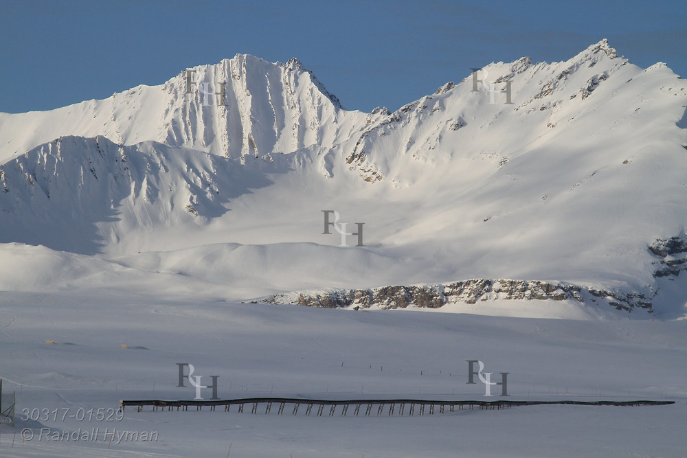 "Raised wooden ""utilidor"" carries pipelines and cables above permafrost at the international science village of Ny-Alesund amid the snowy mountains of Spitsbergen island in April at Kongsfjorden; Svalbard, Norway."