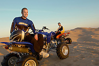 Men standing by quad bikes in desert