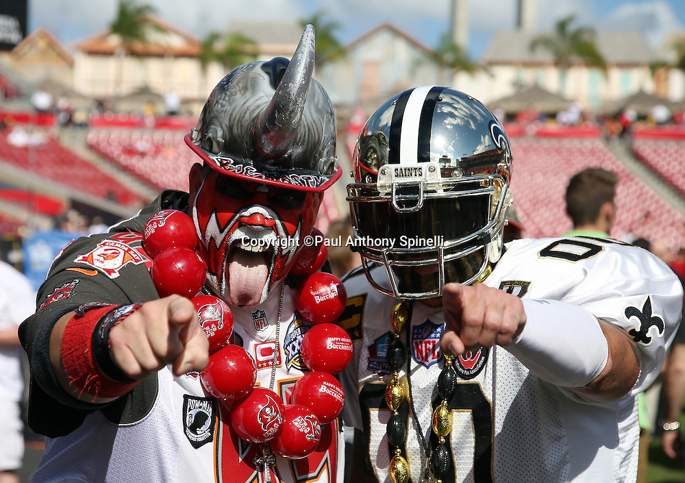 A Tampa Bay Buccaneers and a New Orleans Saints fan dressed up in team related costumes pose for a photo before the 2015 week 14 regular season NFL football game against the New Orleans Saints on Sunday, Dec. 13, 2015 in Tampa, Fla. The Saints won the game 24-17. (©Paul Anthony Spinelli)