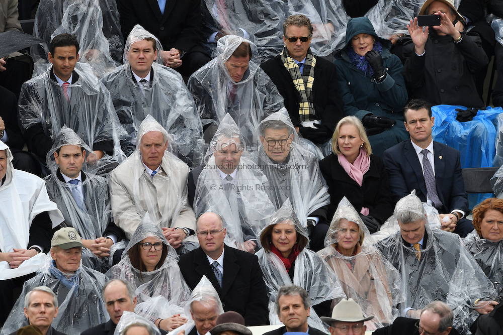 U.S. Senators wearing rain ponchos during a brief rain shower at the President Inaugural Ceremony on Capitol Hill January 20, 2017 in Washington, DC. Donald Trump became the 45th President of the United States in the ceremony.