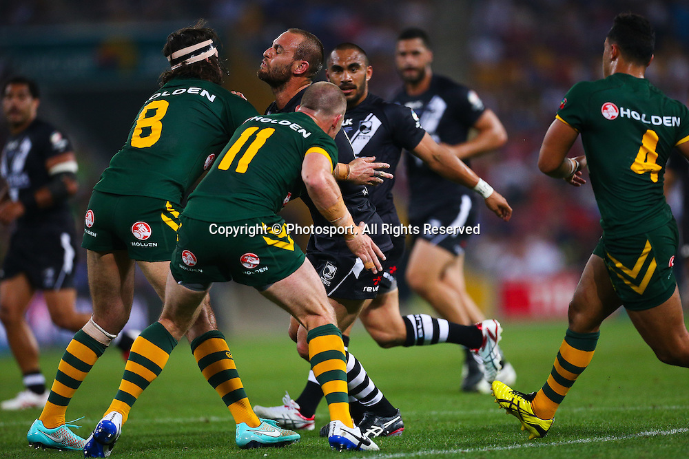 New Zealand Captain Simon Mannering  chargers at the defence of Aaron Woods (L) and Beau Scott (R) during the Four Nations test match between Australia and New Zealand at Suncorp Stadium,  Brisbane Australia on October 25, 2014.