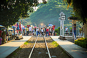 "07 JANUARY 2013 - KANCHANABURI, THAILAND: Tourists photograph a Thai passenger train on ""Bridge On the River Kwai"" in Kanchanaburi, Thailand. Hundreds of thousands of Asian slave laborers and Allied prisoners of war died in World War II making the railway between Bangkok and Rangoon (now Yangon), Burma (now Myanmar) for the Japanese.  Thailand has a very advanced rail system and trains reach all parts of the country.    PHOTO BY JACK KURTZ"