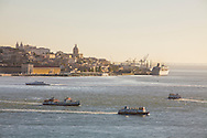 "Lisbon panorama seen from the south bank of Tagus river, in Almada. On the foreground tipical ""cacilheiro"" ships cross the river. At the distance a cruise ship is docked at the cruise terminal."