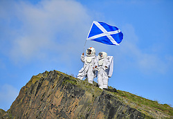 Pictured: Joy Maria Onotu and Sarah Miele hoist the flag on the crags.<br /> <br /> Stars of the Fringe show 'Valentina's Galaxy' appeared as astronauts on iconic Salisbury Crags in Edinburgh in preparation for their show at this year's Edinburgh Fringe.<br /> <br /> © Dave Johnston / EEm