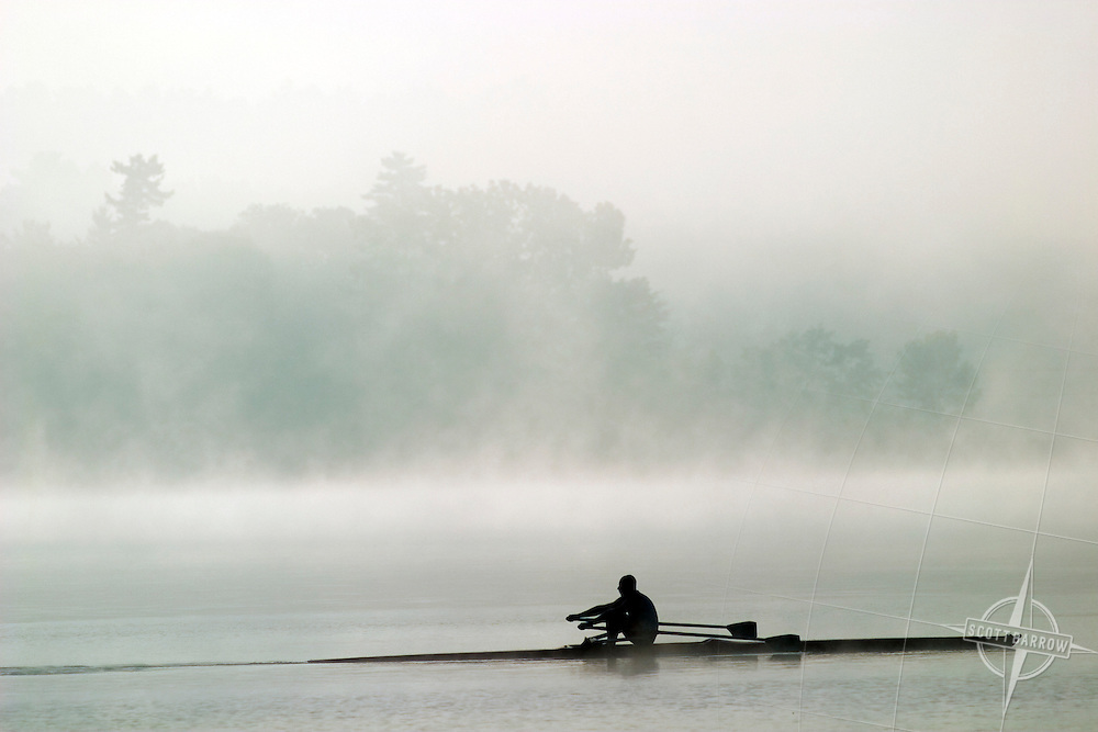 Man rowing in a scull on lake in the early morning fog.