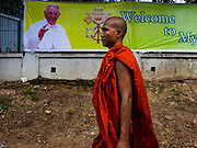 17 NOVEMBER 2017 - YANGON, MYANMAR: A Buddhist monk walks past a poster welcoming Pope Francis to Myanmar. Pope Francis is visiting Myanmar for three days in late November, 2017. He is participating in two Catholic masses and expected to address the Rohingya issue.      PHOTO BY JACK KURTZ