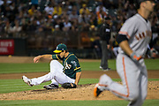 Oakland Athletics relief pitcher Michael Brady (64) falls to the ground after a San Francisco Giants hit buzzes over his head at Oakland Coliseum in Oakland, California, on August 1, 2017. (Stan Olszewski/Special to S.F. Examiner)