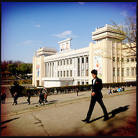 A man walks past an official building with large photos of Kim Il-sung and Kim Jong-il in Pyongyang, North Korea.