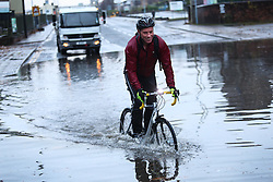© Licensed to London News Pictures. 22/11/2016. Rotherham, UK. A cyclist rides through a flooded road in Rotherham, South Yorkshire, after a river broke it's banks last night. Storm Angus has brought heavy wind and rain to much of the UK this week with flooding seen all over. Photo credit : Ian Hinchliffe/LNP