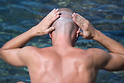 male person putting on and adjusting goggles before diving in the water