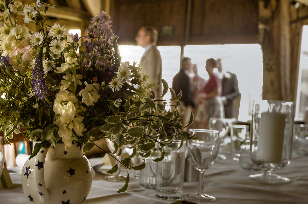 Table setting at wedding with flowers and guests