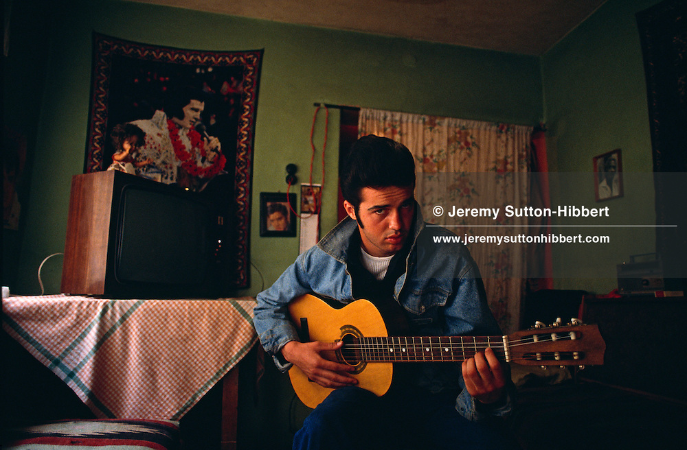 Denis Morina, the 'Albanian Elvis Presley', in his home with borrowed guitar. His favourite Elvis song was 'In The Ghetto'. Tirana, Albania, 1992.