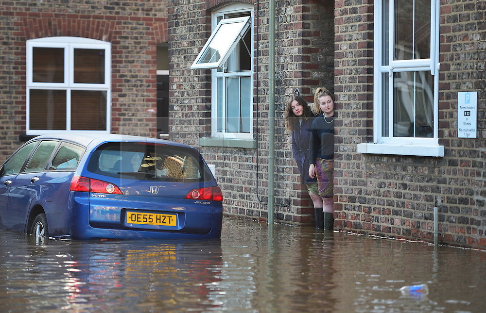 © Licensed to London News Pictures. 27/12/2015. York, UK.  Two residents look out from their property at floodwater in York City centre. Large areas of the North of England have been hit by severe flooding following unusually heavy rainfall in December. Photo credit: Ben Cawthra/LNP