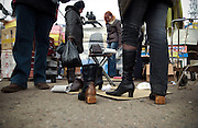 Women try on shoes and boots at the market surrounding the Dynamo Minsk stadium on March 18, 2009.