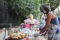 "ROME, ITALY - 3 JULY 2016: (L-R) Gipsy Queen member Codruta Balteau (24) and Aninfa Hokic (31) prepare typical Roma dishes at their food stand at the iFest, an alternative music festival  in Rome, Italy, on July 3rd 2016.<br /> <br /> The Gipsy Queens are a travelling catering business founded by Roma women in Rome.<br /> <br /> In 2015 Arci Solidarietà, an independent association for the promotion of social development, launched the ""Tavolo delle donne rom"" (Round table of Roma women) to both incentivise the process of integration of Roma in the city of Rome and to strengthen the Roma women's self-esteem in the context of a culture tied to patriarchal models. The ""Gipsy Queens"" project was founded by ten Roma women in July 2015 after an event organised together with Arci Solidarietà in the Candoni Roma camp in the Magliana, a neighbourhood in the South-West periphery of Rome, during which people were invited to dance and eat Roma cuisine. The goal of the Gipsy Queen travelling catering business is to support equal opportunities and female entrepreneurship among Roma women, who are often relegated to the roles of wives and mothers."