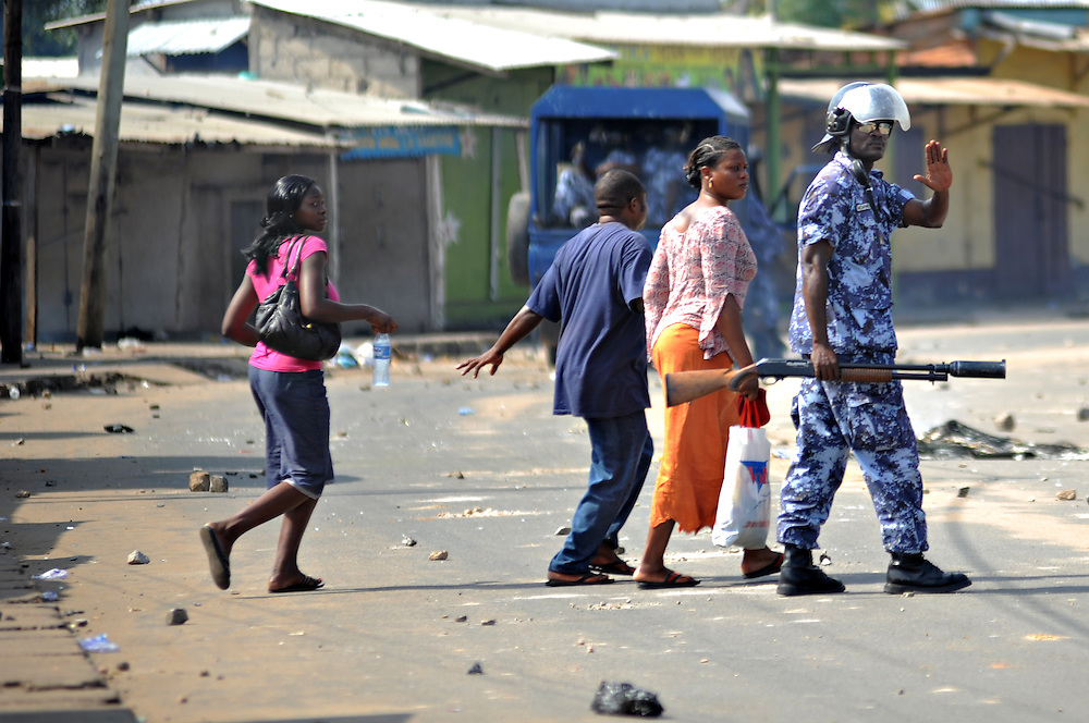 LOME, TOGO - 12-10-05   - A gendarme helps passersby to safety as protesters clashed with police in Lomé on October 5. A peaceful protest was scheduled by opposition groups, but their route was blocked by police.  For months, opposition parties have been calling for the departure of president Faure Gnassingbe, whose family has been in power for over 40 years.   Photo by Daniel Hayduk