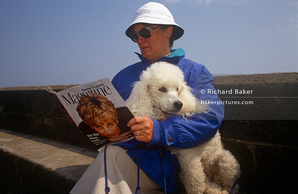 A 1990s lady sits with her pet poodle on a sea wall reading the Sunday Express magazine that features Princess of Wales on the cover, on 19th July 1993, at Scarborough, North Yorkshire, England.