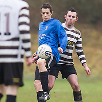 Turnpike Rovers Brian Shannon holds up the ball watched by Moher Celtic's Kevin Scales